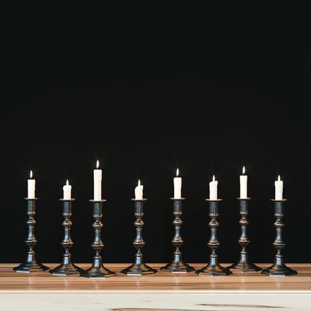 shabat: Varios candelabros de época sobre mesilla de noche de madera contra el fondo de la pared negro. Las velas se queman. 3d