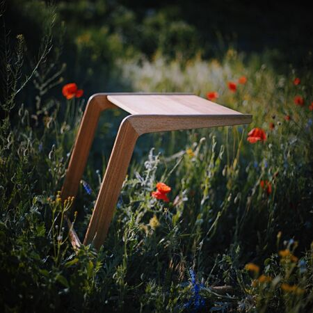 Wood minimalistic coffee table on grass with flowers Foto de archivo - 125475409