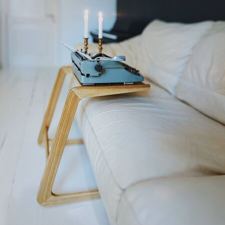 Wood minimalistic coffee table with vintage typewriter in white interior Foto de archivo - 125475412