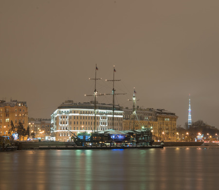 Fine-dining restaurant The Flying Dutchman, moored at the quay Mytninskaya in St. Petersburg. Three-masted sailing ship, a copy of a Dutch ship Amsterdam (1748). Night view from the Spit of Vasilievsky Island