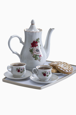 tea and biscuits: a tray with two cups of tea and tea biscuits