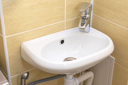 small white sink, a large stainless steel faucet, plumbing pipes below and a hygienic shower Stock Photo