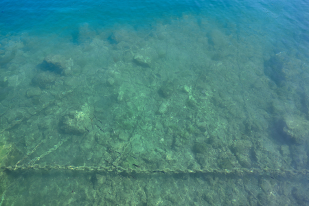In the clear water you can see the seabed next to the quay, the metal chains, stones and fishes Stock Photo
