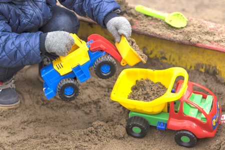 Children in warm winter clothes play in the sandbox close-up