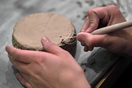 The manufacture of pottery, hands with the tool and the product close-up