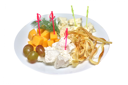 Various cheeses with greens and grapes on white plates, closeup isolated 免版税图像