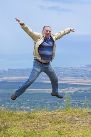 Middle-aged man jumping arms and legs spread out against the background of the view from the mountain