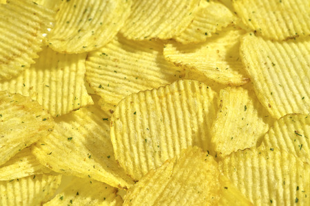 Corrugated potato chips with green onions, close-up food background, texture
