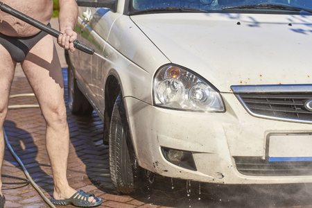 A man in dark swimming trunks on the street washes a white car Standard-Bild