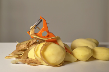 Peeled raw potatoes, peeling potatoes and a peeler on a white background close-up