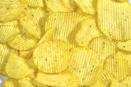 Corrugated potato chips, close-up food background, texture Reklamní fotografie