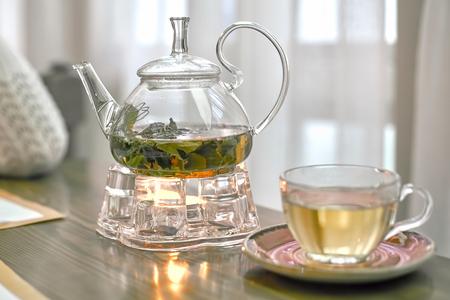 Transparente Teekanne mit grünem Tee auf einem Ständer mit Kerze, Nahaufnahme Standard-Bild