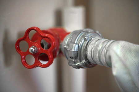 Connection of a fire hose with a red fire cock, close-up Stock Photo