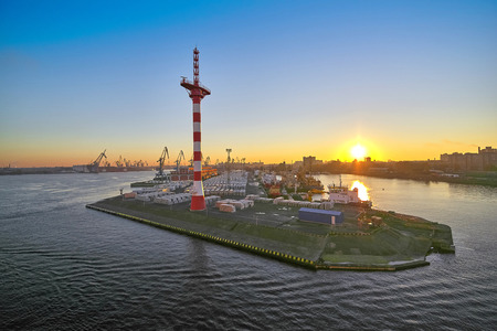 Pier with mast of navigation equipment and cargo berth of ships, sunrise