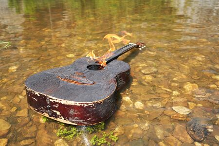 Dogara old acoustic guitar floats on the water. Incendiary music, the crisis of the genre, the end of a career Stock Photo