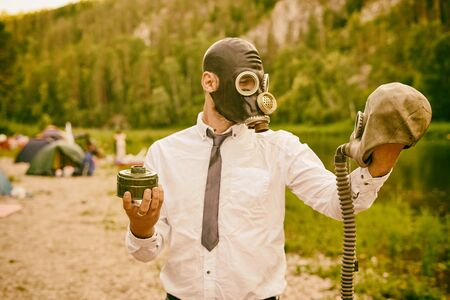 Violation of ecology. A man in a white shirt, tie and gas mask against the backdrop of a mountain river and a tent camp is holding a second gas mask. Toning