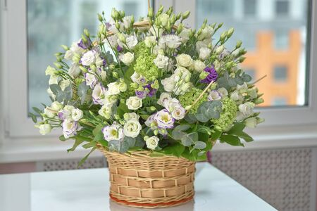 Wicker basket with flowers on a white table, a festive bouquet close-up