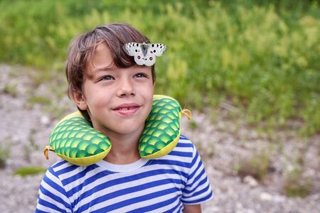 A large white butterfly spread its wings sitting on the head of a child, close-up, place for text