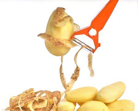 Peeled raw potatoes, peeling potatoes and a peeler on a white background close-up