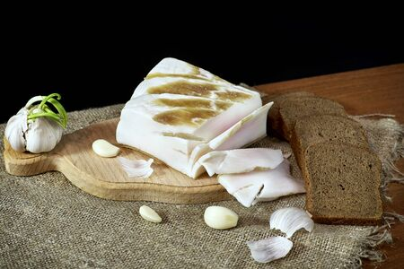 Bread lard and garlic on wooden board against burlap background
