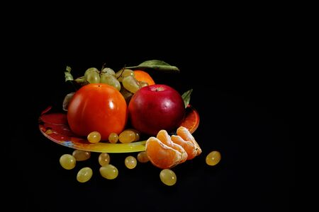Bodegón con frutas sobre fondo negro, espacio para texto