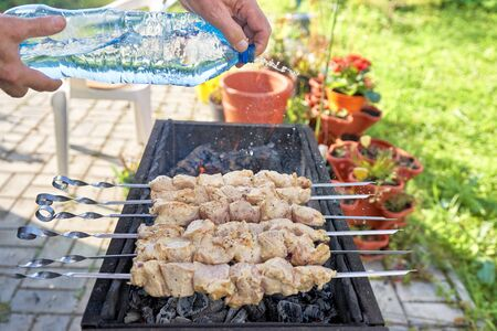 Cooking kebab. Hands with a bottle of water pour meat over hot coals Фото со стока - 129784956