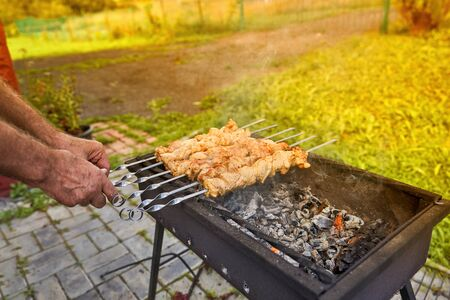 Cooking kebab, toned. Hands hold skewers with raw meat over hot coals Фото со стока - 129785356