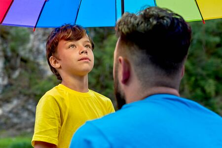 Father and son under a rainbow color umbrella. Fathers day in Nature