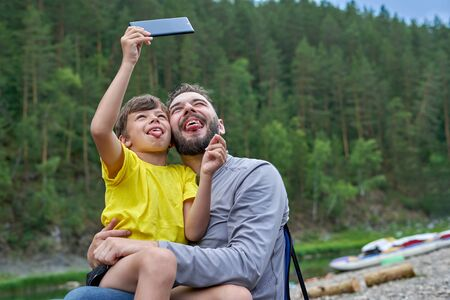 Father and son take pictures of themselves on a smartphone, show grimaces and stick their tongue out onto the camera. Tourists by the river on a summer day Stock fotó