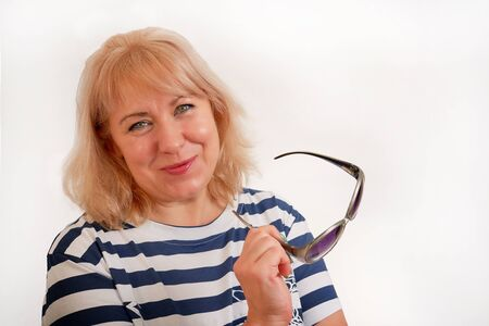 Pretty middle-aged blonde with green eyes smiles at the camera, holds sunglasses in her hands