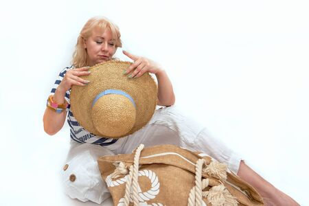 A middle-aged blonde sits with a large beach hat on a white background. Place for text 写真素材