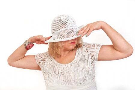 Pretty middle-aged blonde in a white hat and a sweater in a net, isolate. Half-length portrait with hands raised to the head 写真素材