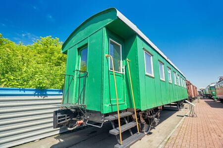 Old green passenger railway carriage on rails at the station near the platform, passenger transportation, close-up