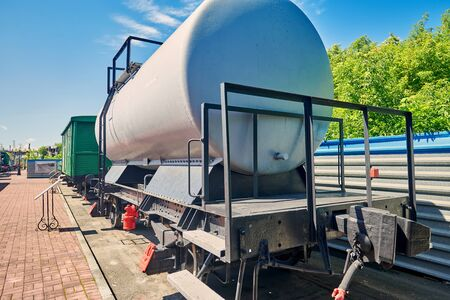Railroad tanker on rails at the station near the platform, Cargo transportation. Sunny summer day. wide angle close up 写真素材