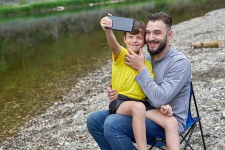 Young dad and son are smiling while making selfie on a mobile phone camera. A man is pulling a boy's smile with his fingers Stock fotó