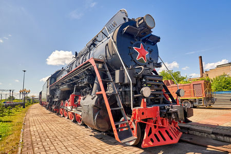 Old steam train on the rails. Close-up on a background of blue sky on a summer sunny day