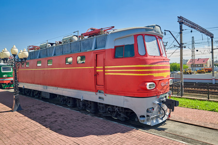 Old red electric locomotive on rails at the station near the platform, freight. Sunny summer day. wide angle close up