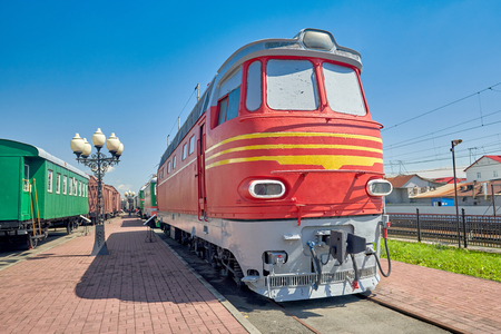 Old red soviet diesel locomotive on rails. Old railway cars at the station near the platform
