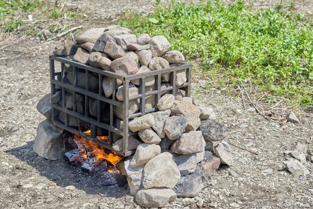 Heated stones using a bonfire in nature, preparing a camp bath. Firewood burns under a pile of stones