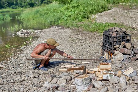 A young man with a naked torso with a stick makes a fire under a pile of stones. Preparation of a bath on the river bank, summer sunny day Reklamní fotografie
