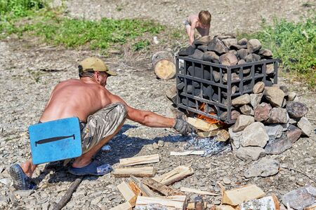 A young man with a naked torso throws firewood into a bonfire under a pile of stones. Preparing a bath in the forest, summer sunny day