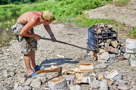 A guy with a naked torso prepares a hiking bath on the river bank, summer sunny day