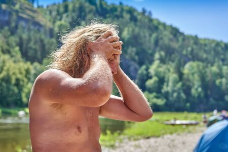 An elderly tanned man with long hair in despair clutched his head in his hands. Hiking against the backdrop of nature on a sunny summer day
