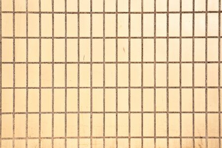 Background from dirty light yellow rectangular ceramic tiles on a cement basis, building texture