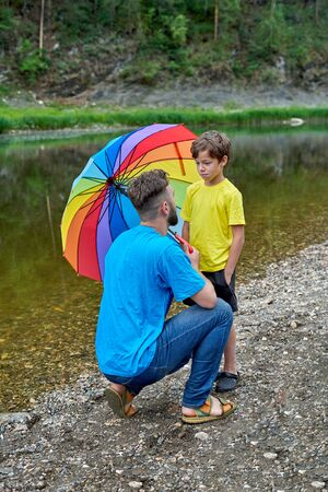 Fathers Day in nature. The shore of a mountain river, a man and a boy with an LGBT umbrella