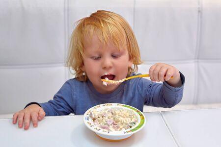 Un niño de tres años, un caucásico de pelo rojo se sienta en una mesa y come con una cuchara de un plato, su boca está sucia de comida
