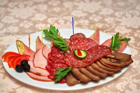 Sliced ??meat delicacies on a white plate, decorated with olives and herbs with vegetables