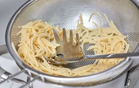 A fragment of a colander with leftover spaghetti pasta, fast cooking, close-up Stok Fotoğraf