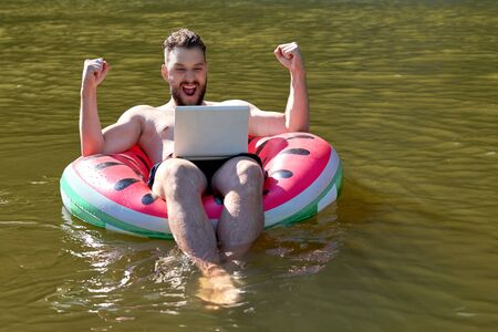 A blogger or freelancer with a laptop floats on a rubber ring. Emotion of delight and joy Foto de archivo - 133384143