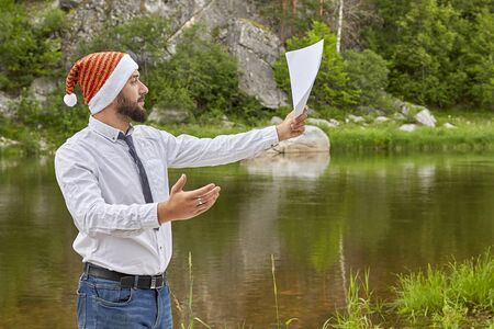 A man in a white shirt, tie and Santa hat holds in his hand a blank sheet of paper on the background of a mountain river on a summer day. Foto de archivo - 133384150